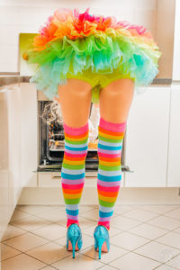 A blond young partygirl wearing her sexy gogo dancer outfit at home. A little bit upskirt at the kitchen with a panty and colorful overknees